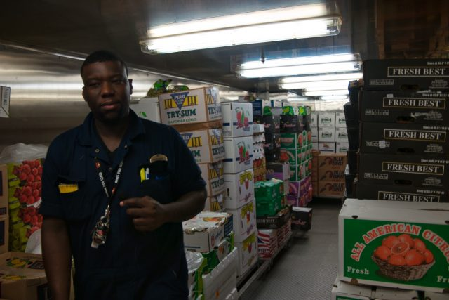 Behind the Scenes Ship Tour - Tour guide surrounded by fresh produce