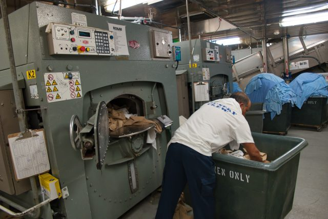 Behind the Scenes Ship Tour - Laundry crew loading a dryer.