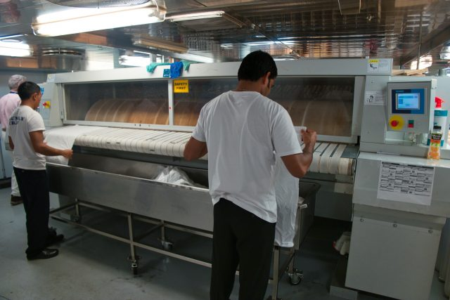 Behind the Scenes Ship Tour - Laundry crew running pillow cases through a machine.
